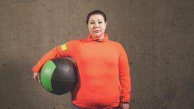 Mulher excesso de peso agradável com a bola do exercício isolada no fundo cinzento vídeos de arquivo