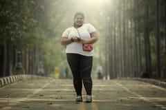 Mulher excesso de peso com o smartphone na estrada Fotografia de Stock Royalty Free