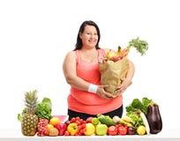 Mulher excesso de peso com um saco de mantimentos atrás de uma tabela com fruto imagens de stock royalty free