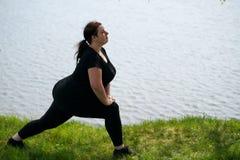 Mulher excesso de peso nova que faz a ioga da manh? fotografia de stock