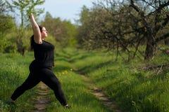 Mulher excesso de peso que faz a ioga no parque da manh? foto de stock royalty free