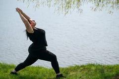 Mulher excesso de peso que faz a ioga, relaxando perto do lago imagem de stock royalty free