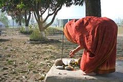 A mulher executa o ritual tradicional da adoração da manhã no pátio fotografia de stock royalty free