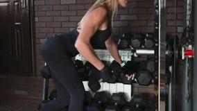 A mulher executa um exercício arqueado da fileira do peso do braço vídeos de arquivo