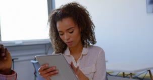 Mulher executiva da misturado-raça bonita que usa a tabuleta digital no escritório moderno 4k filme