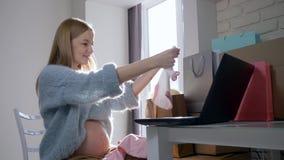 Mulher expectante bonito feliz com abdômen despido que considera a roupa nova para a criança futura comprada no Internet que sent video estoque