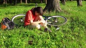 A mulher experimenta a dor na articulação do joelho, sangrando a ferida, ferimento da bicicleta filme