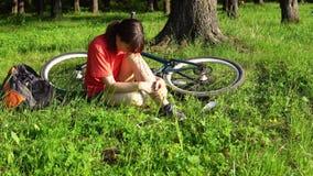A mulher experimenta a dor na articulação do joelho, sangrando a ferida, ferimento da bicicleta vídeos de arquivo