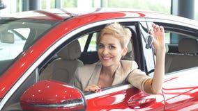 Mulher extático do motorista que sorri e que mostra a chave nova ao sentar-se na sala de exposições do carro vídeos de arquivo