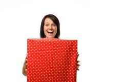 Mulher extático feliz que guarda um grande presente vermelho Fotos de Stock Royalty Free