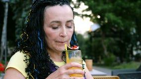 Mulher extravagante superior que bebe um cocktail de fruto da paixão que senta-se em um café da rua no parque entre as árvores vídeos de arquivo