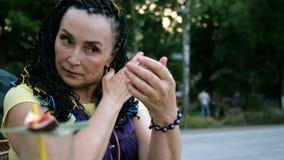 A mulher extravagante superior que senta-se e endireita o cabelo que olha em um espelho pequeno no parque entre as árvores filme
