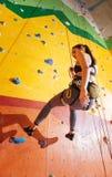 Mulher Extremal que escala acima a parede alaranjada no gym imagens de stock royalty free