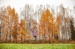 A mulher exulta na chegada do outono A menina em um campo perto da floresta amarela do outono, outono veio, a emoção da alegria foto de stock