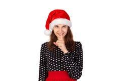 A mulher eyed largamente pedir o silêncio ou o secretismo com o dedo nos bordos menina emocional no chapéu do Natal de Papai Noel imagem de stock