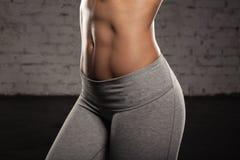 A mulher fêmea da aptidão com corpo muscular, faz seu exercício, Abs, abdominals Fotografia de Stock Royalty Free