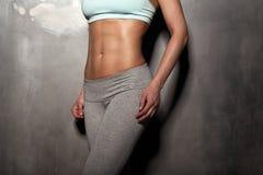 A mulher fêmea da aptidão com corpo muscular, faz seu exercício, Abs, abdominals Fotos de Stock Royalty Free