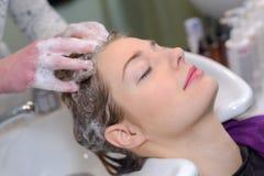 Mulher fêmea nova que tem o cabelo lavado no salão de beleza imagem de stock
