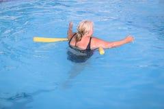 A mulher fêmea superior aferra-se a um dispositivo de flutuação em uma piscina para aprender como nadar fotografia de stock
