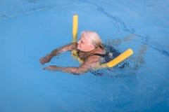 A mulher fêmea superior aferra-se a um dispositivo de flutuação em uma piscina para aprender como nadar foto de stock