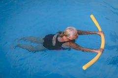 A mulher fêmea superior aferra-se a um dispositivo de flutuação em uma piscina para aprender como nadar imagens de stock royalty free