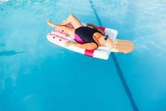 Mulher fêmea superior com mentiras brilhantes dos vidros de sol em um flutuador dado forma da piscina gelado inflável fotografia de stock