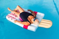 Mulher fêmea superior com mentiras brilhantes dos vidros de sol em um flutuador dado forma da piscina gelado inflável imagens de stock royalty free