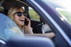 A mulher fala no telefone no carro fotos de stock