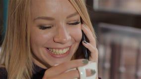 A mulher fala no telefone no café vídeos de arquivo