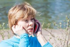 A mulher fala pelo telefone contra a água imagem de stock