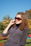 A mulher fala pelo telefone na tarde Imagens de Stock