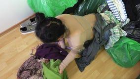 Mulher fatigante perto da pilha da roupa velha filme