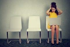 Mulher fatigante que senta-se na cadeira com portátil foto de stock royalty free