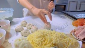 A mulher faz bolas da massa para a pizza com ingredientes diferentes Entrega o close-up filme