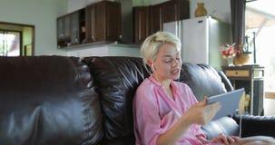 A mulher faz a chamada video em linha usando a sala de Sit On Coach In Living do tablet pc, Internet falador de sorriso da menina filme