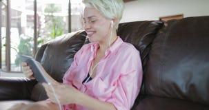 A mulher faz a chamada video em linha usando a sala de Sit On Coach In Living do tablet pc, Internet falador de sorriso da menina video estoque