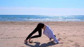 A mulher faz descendente - pose do cão do revestimento na ioga no exercício do esporte da praia da areia do mar vídeos de arquivo