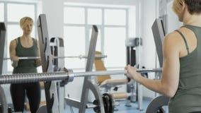 A mulher faz exercícios com o barbell para o bíceps video estoque