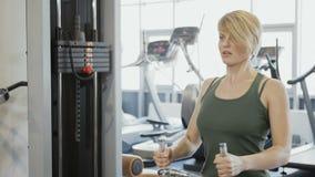 A mulher faz exercícios para ela para trás no gym vídeos de arquivo