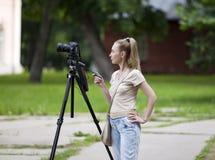 A mulher faz fotografias no parque na câmera de reflexo de uma montagem com o controlo a distância Fotos de Stock Royalty Free