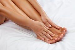 A mulher faz massagens seus pés cansados imagem de stock