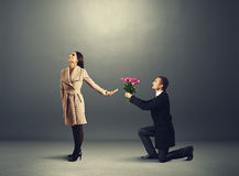 A mulher faz não olhando o homem com flores Fotografia de Stock Royalty Free