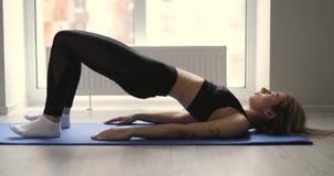 A mulher faz o exercício dos pilates na manhã em casa vídeos de arquivo