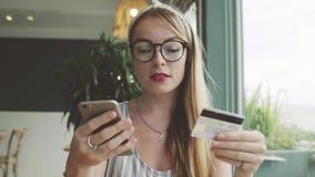 A mulher faz o pagamento com cartão e telefone celular de crédito Operação bancária em linha vídeos de arquivo