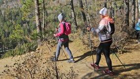 A mulher faz o passeio nórdico na natureza As meninas e as crianças usam varas trekking e polos nórdicos, trouxas cursos da famíl video estoque