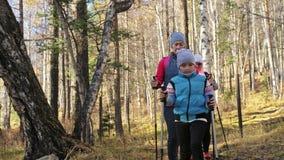 A mulher faz o passeio nórdico na natureza As meninas e as crianças usam varas trekking e polos nórdicos, trouxas cursos da famíl vídeos de arquivo