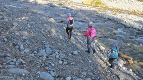 A mulher faz o passeio nórdico na natureza perto do rio da montanha As meninas e as crianças usam varas trekking e polos nórdicos filme
