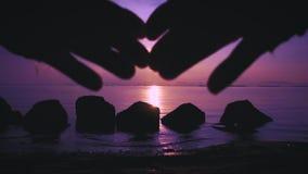 A mulher faz o quadro da forma do coração com os dedos ao paisagem-nascer do sol espetacular na praia video estoque