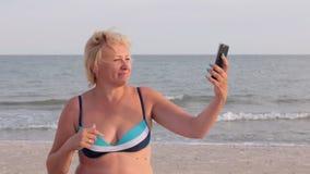 A mulher faz o selfie na praia contra o contexto das ondas filme
