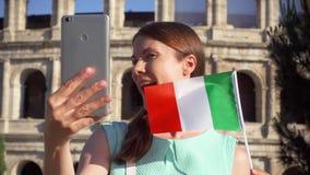 A mulher faz o selfie no móbil perto de Colosseum em Roma, Itália Bandeira italiana da onda do adolescente no movimento lento filme